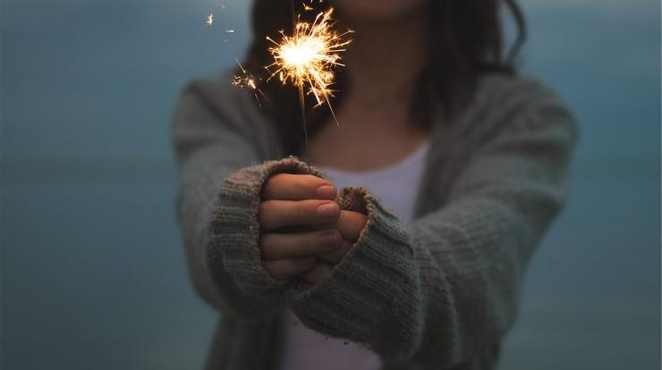 A woman holding a sparkler at dusk