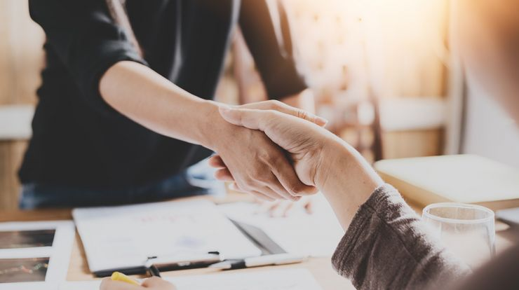 Two people shaking hands over paperwork