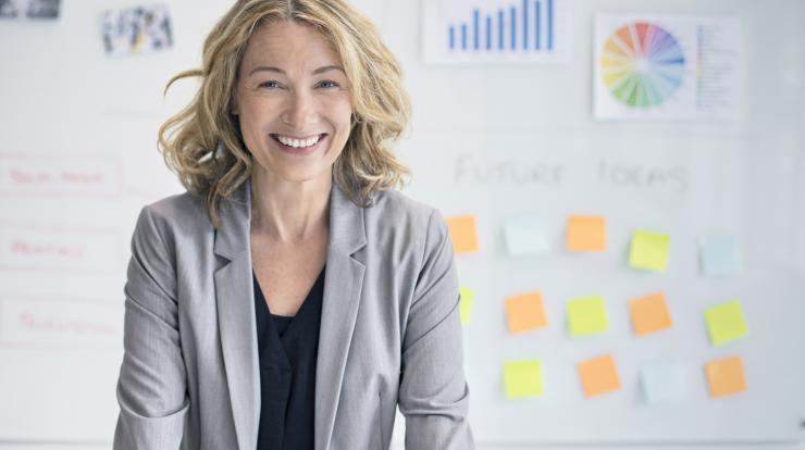 Bold mature woman worker in front of white board