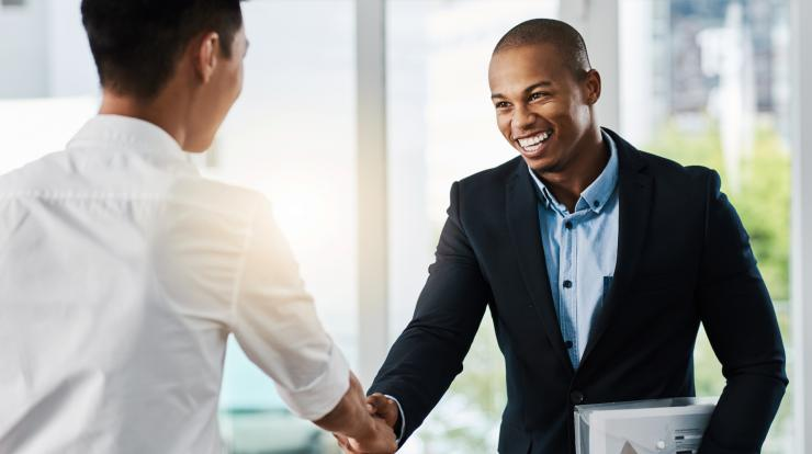 Two young business men shaking hands