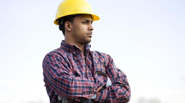 Young male construction worker thinking