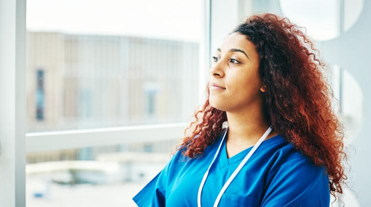 Young female nurse looking out window thinking about her future