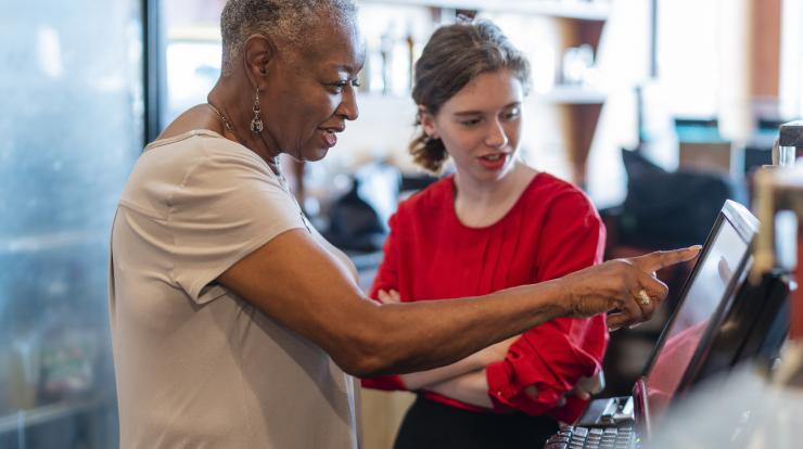 woman restaurant owner showing younger employee how to do something