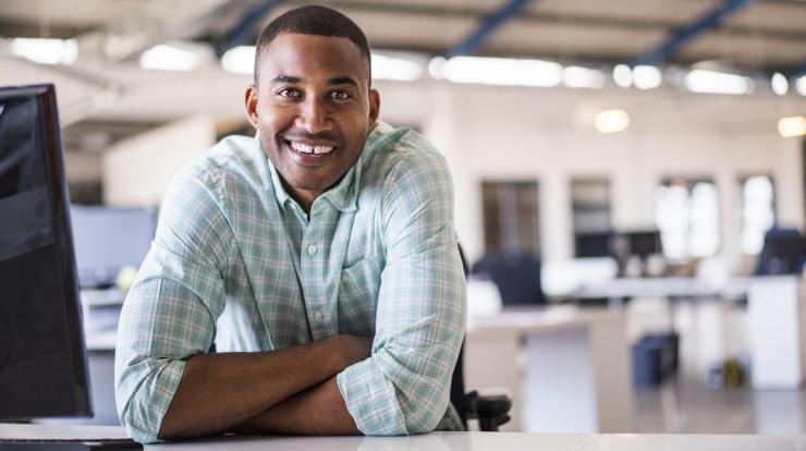 young man working at his laptop and smiling