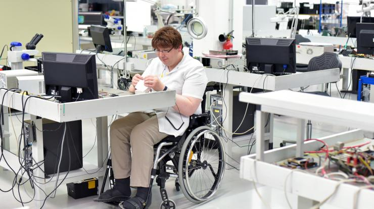 man in wheelchair working in high-tech office