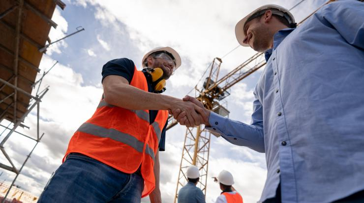 Construction worker shaking hands with foreman on job site