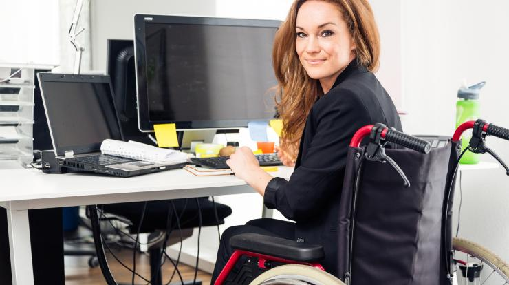 Woman in wheelchair at desk in office