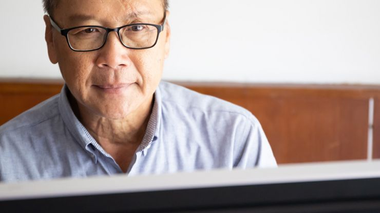 Asian man wearing a blue shirt using a laptop
