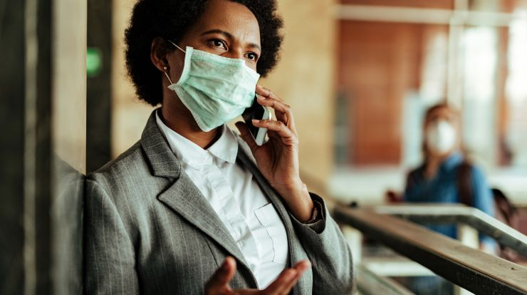 African American businesswomen with face mask talking on the phone at a railroad station lobby