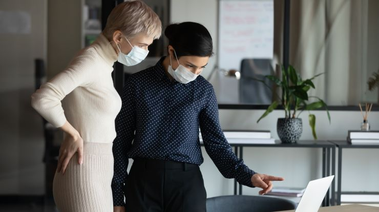 Focused two women in medical protective masks working in office.