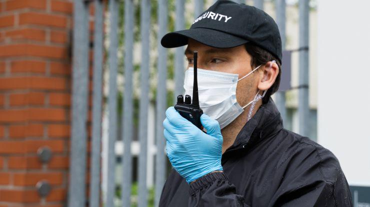 Security Guard in face mask talking on walkie talkie.