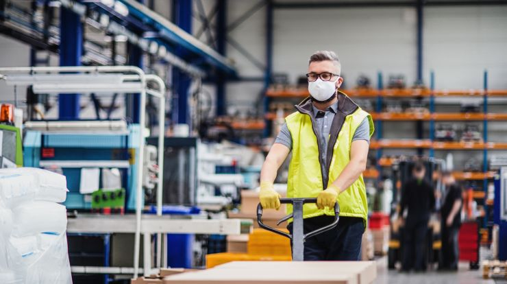 Man worker with protective mask working in an industrial factory or warehouse.