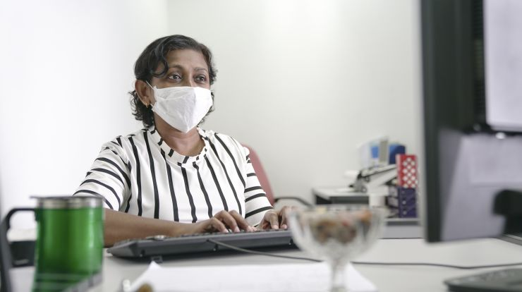 Woman wearing a face mask at a computer in office