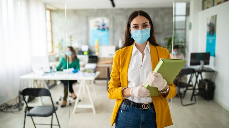 Female office worker wearing yellow jacket and face mask standing outside an office with a person sitting at a desk wearing a face mask.