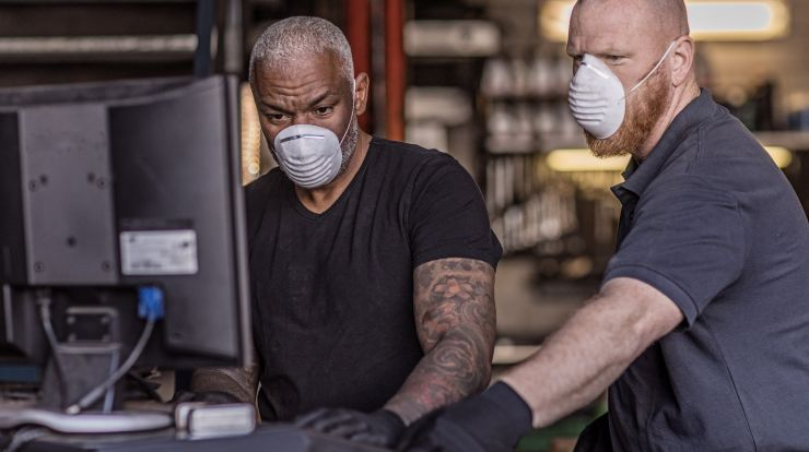 Two men working at a computer wearing masks, one supervising the other.