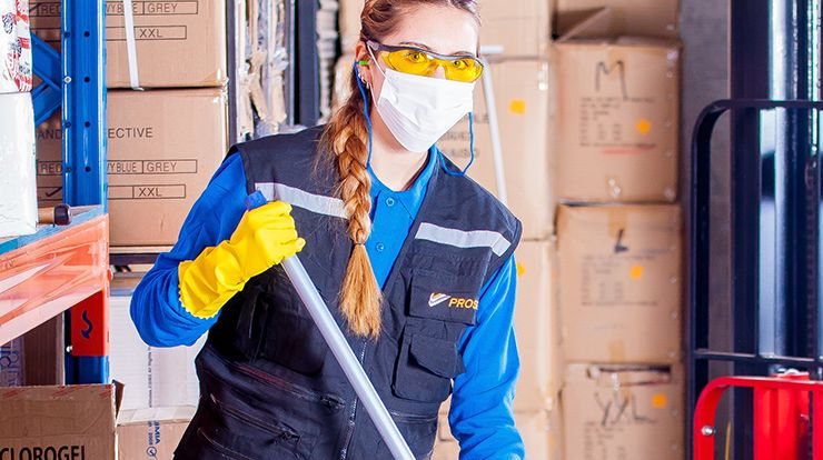 Cleaning worker holding mop in protective gear