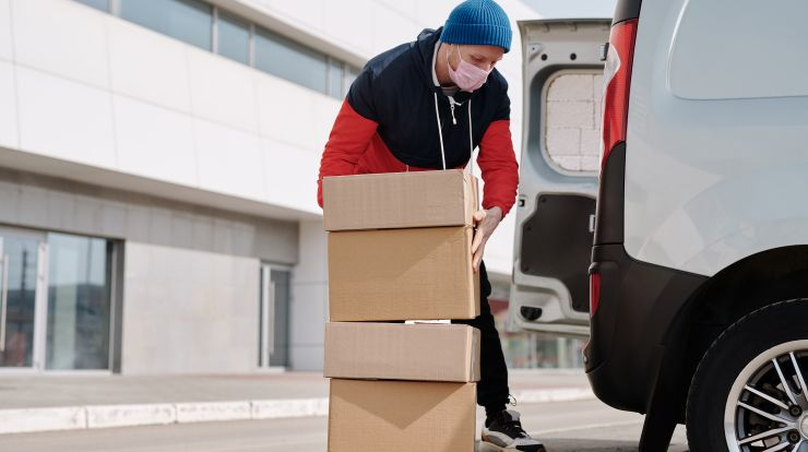Delivery worker wearing a mask loading boxes into the back of a white van.