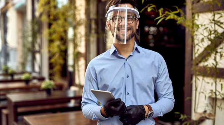 Food service worker in face shield holding tablet in restaurant