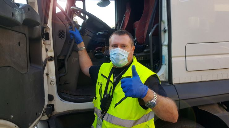 Tractor-Trailer truck driver wearing a face mask and yellow vest getting into truck cab with thumbs up