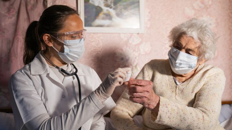 Nursing assistant and patient, both wearing masks