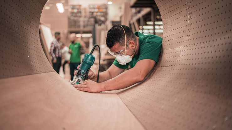 Worker in green shirt wearing a mask