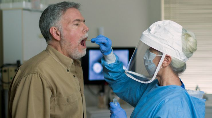 Healthcare worker in a face shield and mask swabbing inside a patient's mouth