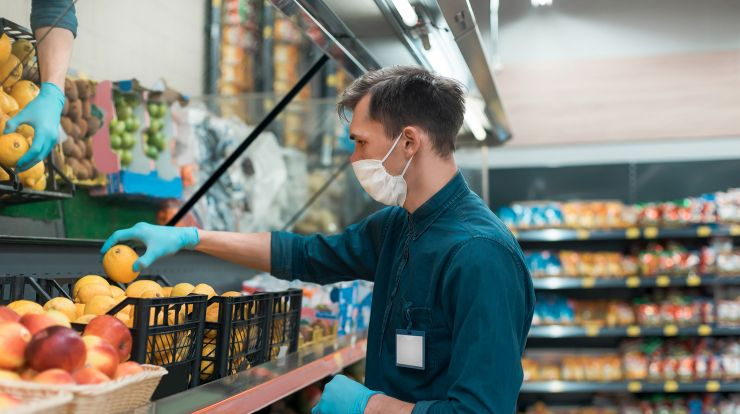 Retail Worker wearing a face mask stocking oranges in a store