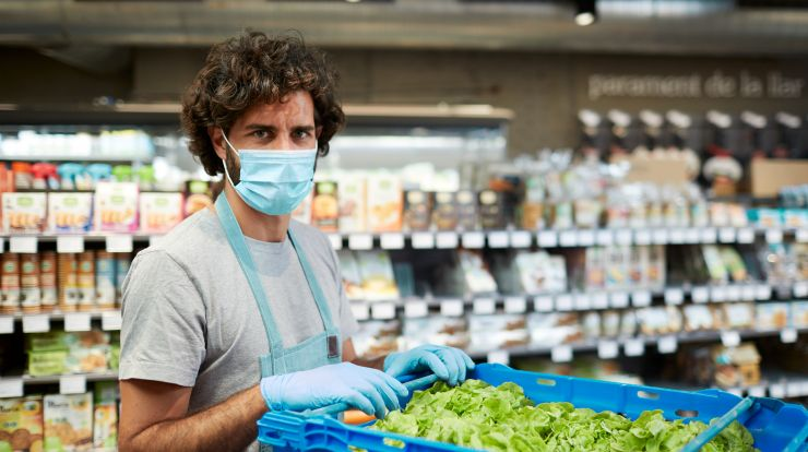 Person standing in grocery store produce section with container of lettuce