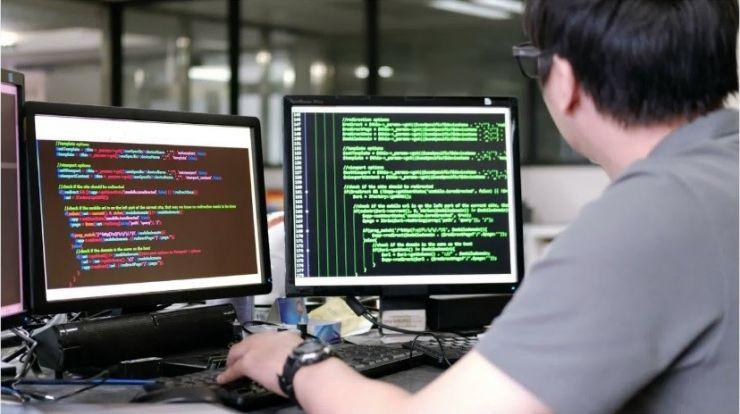 person looking at two computer monitors, keyboarding