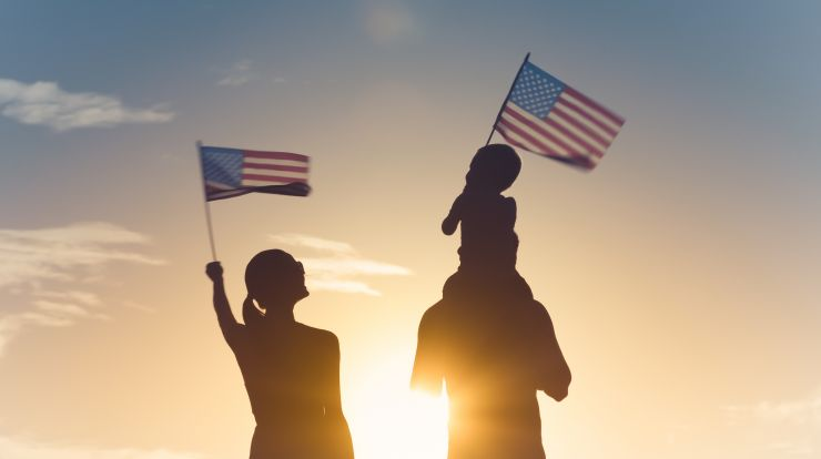 man, woman and child waving U.S. flags silhouette against sunset