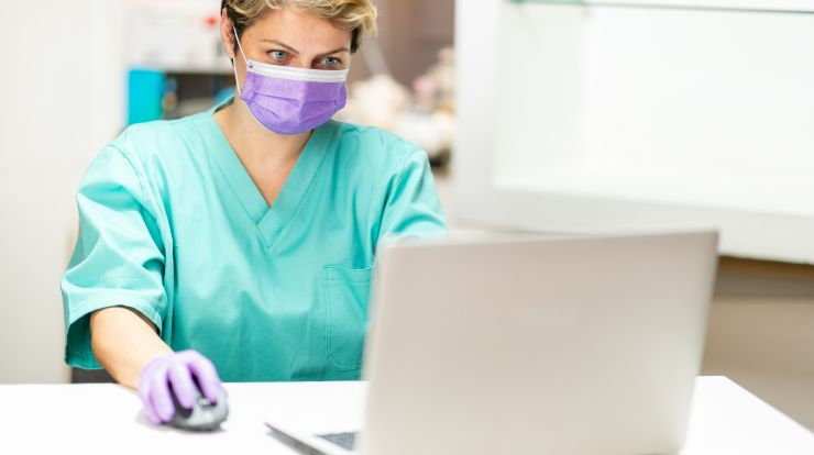 woman in medical setting on laptop, woman wearing mask