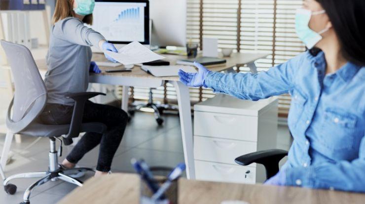 two women in an office setting, both women wearing masks