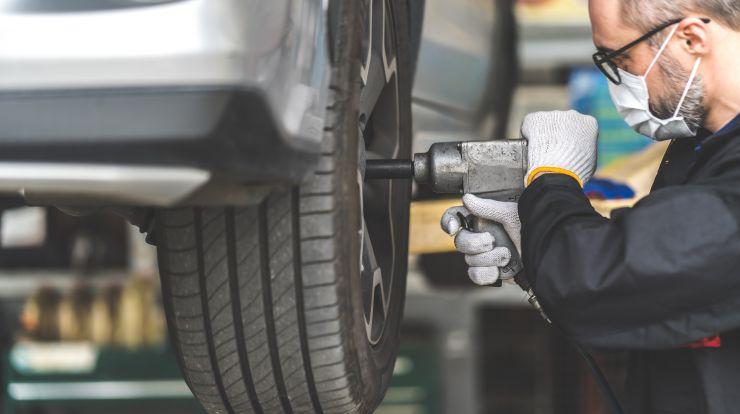 Auto Mechanic working on care tire