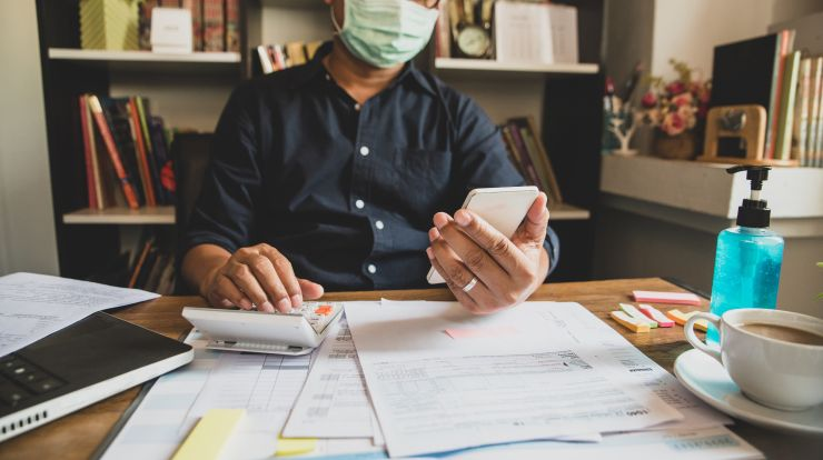 masked person at desk with papers, holding calculator