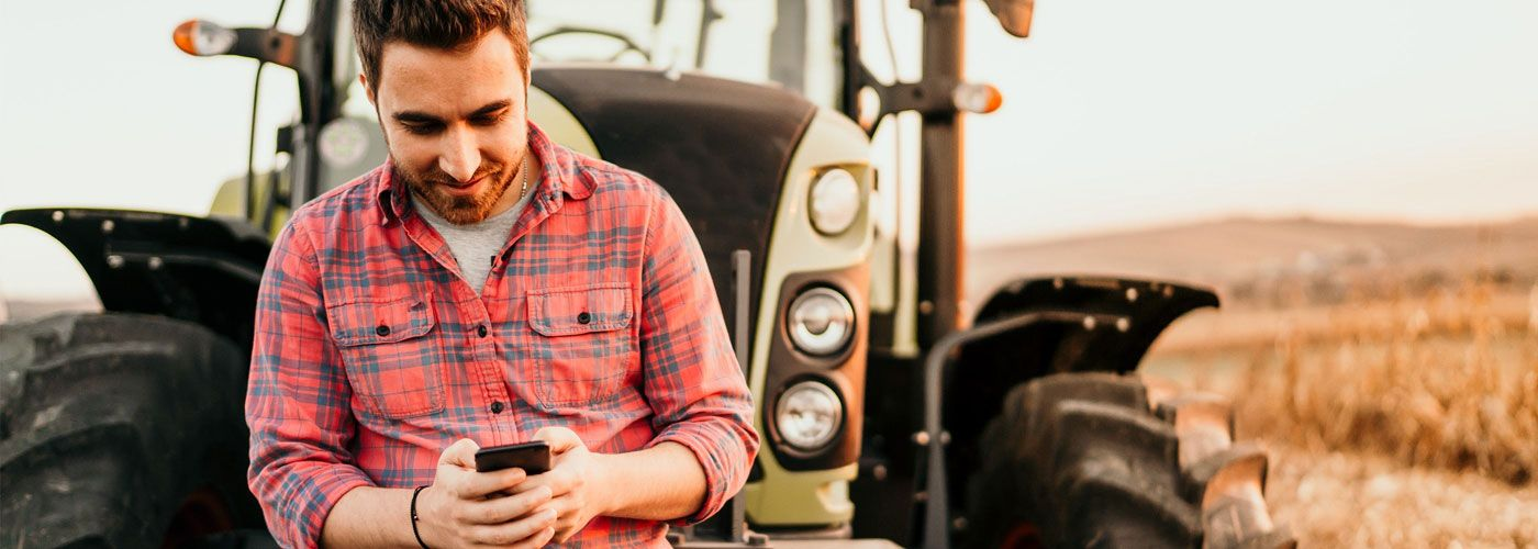Farmer on his mobile phone in front of tractor