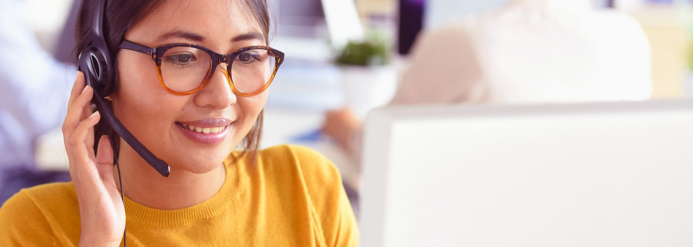woman with headset looking at computer