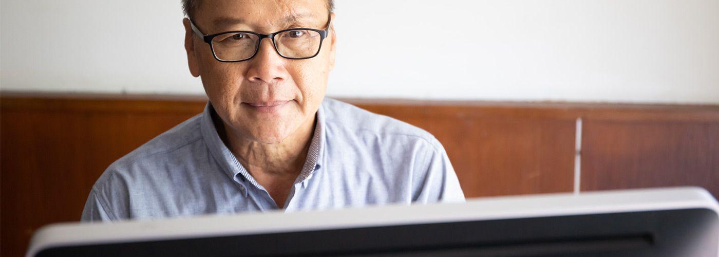 Asian man wearing a blue shirt using a laptop