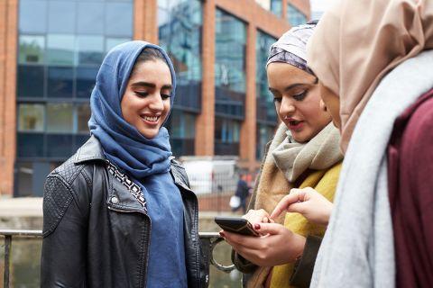 Three women looking at phone