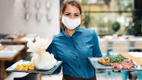 Food Service Worker holding two plates in a restaurant