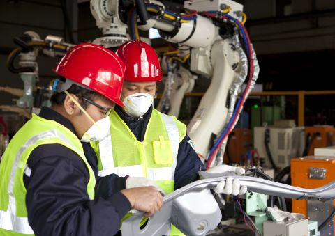Assembly workers inspecting a part